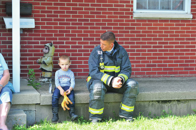 Piqua firefighter John Richard comforts a young boy at the scene of a house fire on First Street in Piqua on Saturday afternoon.