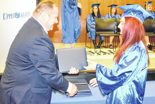 Provided photo Aspire graduate April Finley of Piqua receives her diploma from Upper Valley Career Center Adult Division Director Scott Naill.