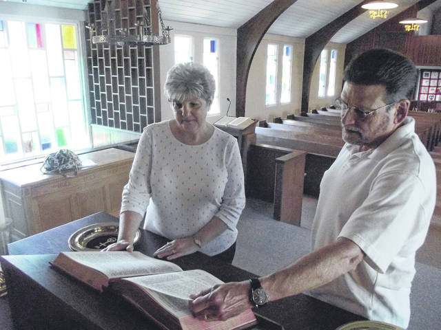 Greenview United Church of Christ Board of Deacons Chairman Shirley Foster, left, and the Rev. Larry Grunden look at the new Bible which has been donated by the Leckey family to the church. The Bible rests on the front altar in the sanctuary. It replaces the Bible destroyed by a fire set by an arsonist on Aug. 21, 2017.