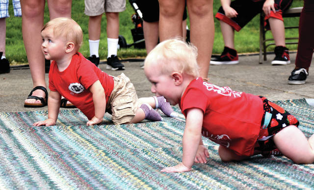 Cody Willoughby | AIM Media Midwest Twelve-month-olds Lee Franer, left, of Fairborn, and Rylan Manson, of Piqua, crawl neck-in-neck during the Diaper Derby, an event held as part of the 42nd Annual Troy Strawberry Festival on Sunday.