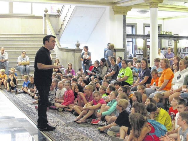 Sam Wildow | Daily Call Scholar Fred Blanco (front left) teaches children about Chautauqua, character development, and acting at the Piqua Public Library on Tuesday. Blanco will be portraying Cesar Chavez, founder of the United Farm Workers labor movement, later this week in an evening performance at Fountain Park.