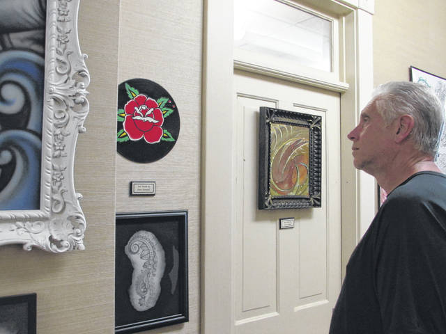 Sam Wildow | Daily Call Jeff Cater of Huber Heights views the Extreme Tattoo Studio art display in the Horace Rollin Gallery on the second floor of the Piqua Public Library, located at 116 High St., on Wednesday.