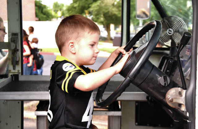"Cody Willoughby | Troy Daily News Archer Eddie, 3, of Piqua honks the horn of a mail truck from the United States Postal Service during the ""Touch-a-Truck"" program on Monday at Troy-Miami County Public Library."