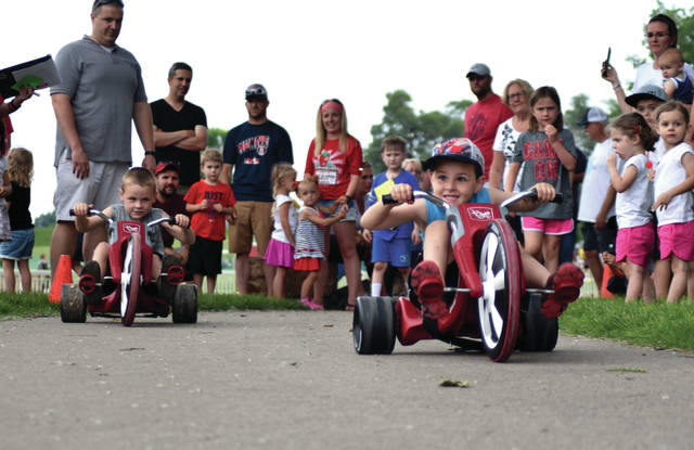 Cody Willoughby | AIM Media Midwest Left to right, Lucas Summers, 5, and Rhys Garrity, 5, both of Troy, compete in the Big Wheel race during the 42nd annual Troy Strawberry Festival opening festivities on Friday at Treasure Island Municipal Park.