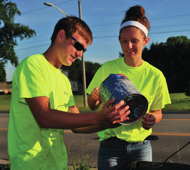 Chase Gambill, left, and Faith King paint a fire hydrant on Co. Rd. 25-A. Gambill, a Bradford High School graduate is a sophomre at Hocking College. He is in his second season as a part-time seasonal worker for Piqua and is studying to obtain h is Class 1 Water Operator license and his goal is to become a full-time City of Piqua employee. King is a freshman at Ohio State.