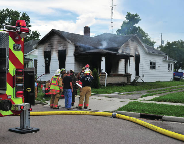 Mike Ullery | Daily Call Firefighter put out hot spots at a residence in the 500 block of South Third Street in Tipp City on Wednesday afternoon.