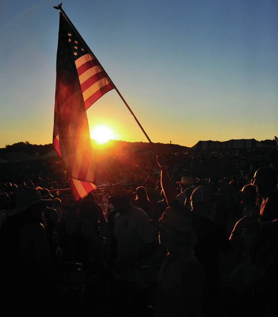 Mike Ullery | Daily Call Fans wave an American flag as the sun sets during County Concert 2018 on Saturday bringing to a close three days of entertainment