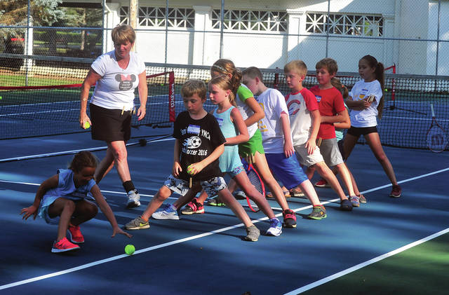 Mike Ullery | Daily Call Youth Tennis Camp participants warm up for the evening's practice session as Bonnie Davis looks on.