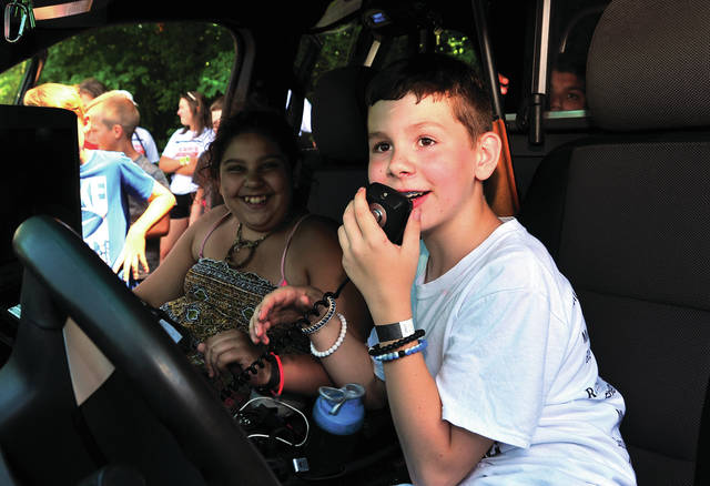 Mike Ullery | Daily Call Bryson Bailey, 12, of West Milton, tries out the PA system in a sheriff's cruiser on Wednesday at the Miami County Sheriff's Department Summer Youth Camp.