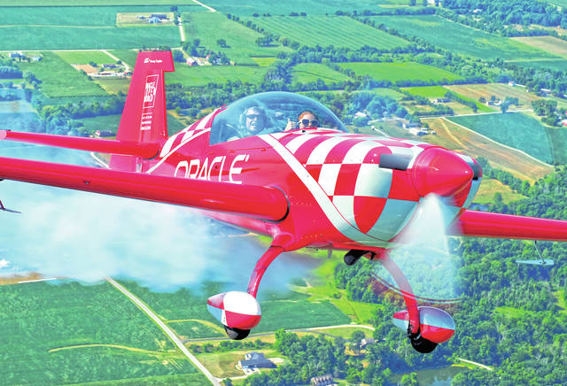 Mike Ullery | Daily Call Kayla Hughes, 14, of Dayton, gives a thumbs-up as she takes a Young Eagles flight with National Aviation Hall of Fame enshrinee Sean D. Tucker in the skies over Piqua on Tuesday morning.