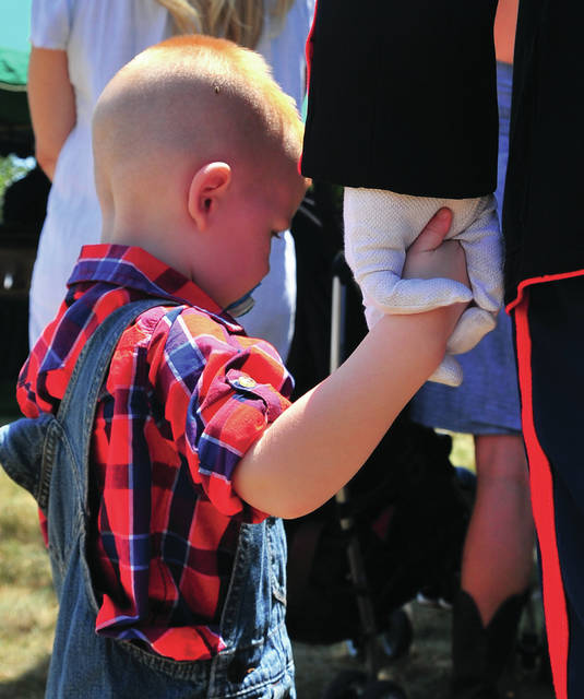 Mike Ullery | Daily Call SGT Phillip Couch, USMC holds his son Macklin, 3, hand during funeral services for Troy firefighter Jason Holfinger, 38, who was laid to rest at Miami Memorial Park in Covington following funeral services at Koinos Christian Fellowship Church in Troy on July 19, 2018. Community members have organized a Go Fund Me account to help provide for the the future for Holfinger's children. SGT Couch was a brother-in-law to Holfinger. He, along with a fellow Marine, performed the flag-folding ceremony at Holfinger's funeral.