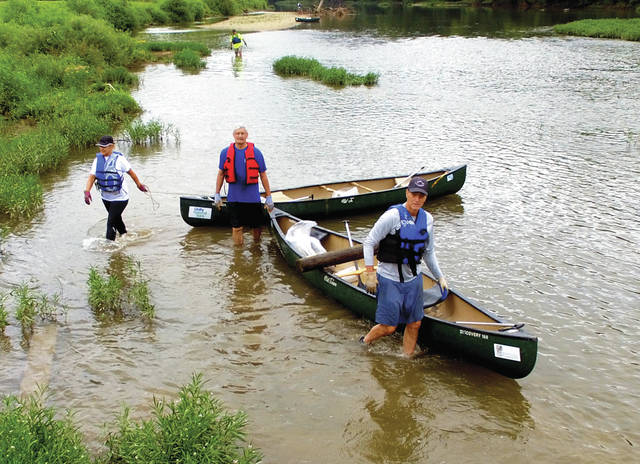 Mike Ullery | Daily Call Mayor Kazy Hinds, Joe Wilson, and Mike Gutmann (left to right) make their way down the Great Miami in Piqua on Saturday picking up trash as part of the 2018 Clean Sweep of the Great Miami River organized by Jeff Lange, president and founder of Protect Our Water Ways (POWW). In addition to those traveling by canoe, several volunteers walked along the banks picking up trash. All debris was transported to a truck at the Piqua Boat & Ski Club ramp waiting to take it to the Miami County Transfer Station for recycling or disposal. The annual river cleanup through Troy, which was scheduled for last Friday, was changed to Aug. 10, due to rain.