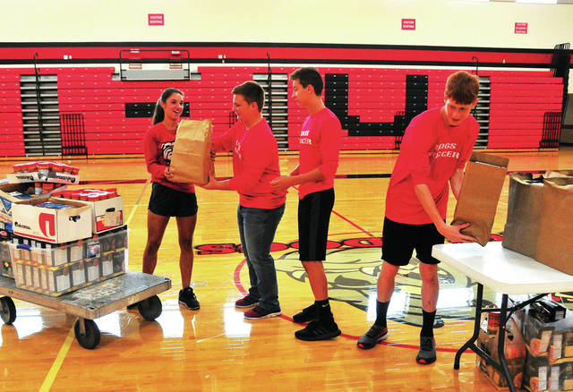 Mike Ullery | AIM Media Midwest Milton-Union soccer seniors Kristen Dickison, Tyler Ezerski, Andrew Besecker, and Bradley Booker transfer food donations to a table in the gym at the high school on Sunday. The donations, 620 and counting, will be delievered to the House of Bread in Dayton on Friday.