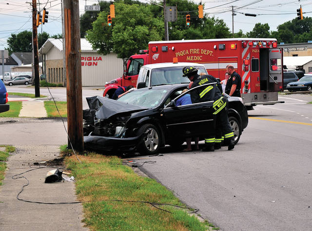 Mike Ullery | Daily Call Firefighters and medics from the Piqua Fire Department tend to two victims of a single-vehicle crash on South Main Street near Clark Avenue on Tuesday afternoon.