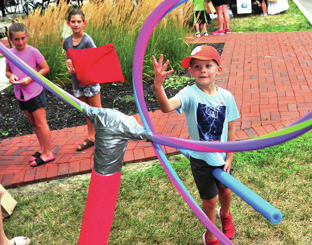 Mike Ullery | Daily Call Cooper Persia, 5, of Cleveland shows his skills at Quidditch training station at the Harry Potter birthday party the Piqua Farmers Market on Thursday.