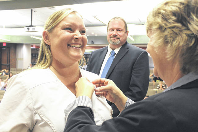 Provided photo Belinda Roop of Troy is pinned by Lori Ludwig, UVCC Adult Division Practical Nursing program director, as UVCC Adult Division Director Scott Naill looks on.