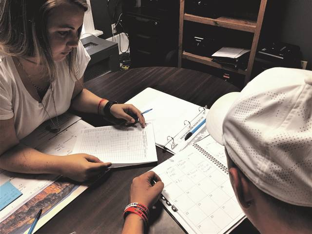 Recovery Program Manager Ashley Lowe reviews the weekly schedule with a resident of Shelby House men's recovery home in Sidney. Planning and accountability are important parts of a successful recovery from addiction.