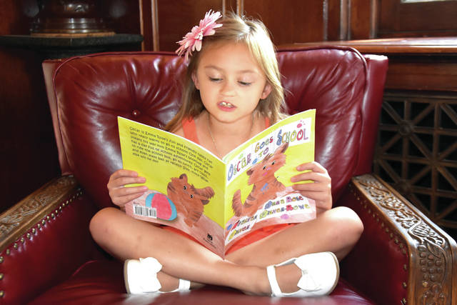 """Cody Willoughby   AIM Media Midwest Emma Rose Fisher-Rowe reads an excerpt from """"Oscar Goes to School,"""" a new book co-written with her mother, Meaghan Fisher, at Troy-Hayner Cultural Center."""