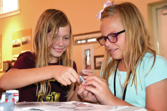 Cody Willoughby | AIM Media Midwest Adrienne Hauk, 9, of Vandalia, and Haley Haddix, 10, of Englewood, brainstorm on the construction of their customized LEGO robot during robotics camp on Monday at WACO Air Museum in Troy.