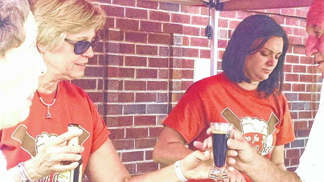 Provided photo Pourers serve up some suds at a past Down a River Down a Beer festival. This year's event will be held Aug. 4, from 6-10 p.m. at Lock 9 Riverfront Park in Piqua.