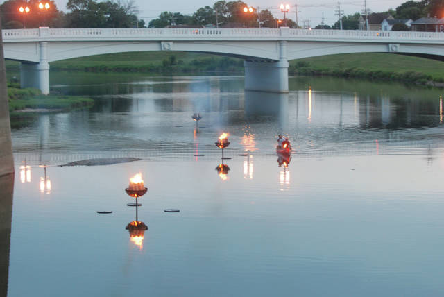 Mike Ullery | AIM Media file photo Jeff Lange and Ron Jackson light five fire rings in the Great Miami River at dusk as part of the Down the River, Down a Beer celebration at Lock 9 Park in Piqua in 2015.