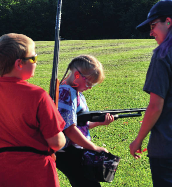 Addison Lunsford, 9, of Troy, reaches for a shell as she prepares to get some trap shooting practice in at the Piqua Fish and Game last month. Lunsford is a member of the Miami County Trap Shooters 4-H Club.