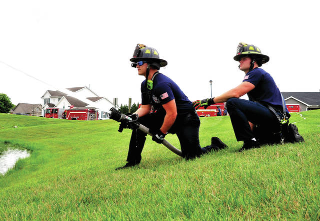 Mike Ullery | Dail Call Piqua firefighters Corbin Peltier and Tony Sutter man a hand line during a day of pump training for Shift 1 at a pond on the west side of the city on Wednesday afternoon.