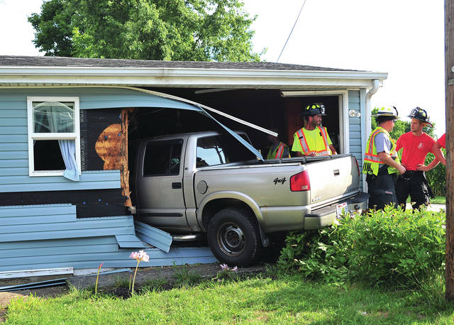 Mike Ullery | Daily Call Firefighters from Covington inspect damage to a home at 9495 W. U.S. Route 36, west of Covington on Thursday evening after a pickup truck crashed into the residence.