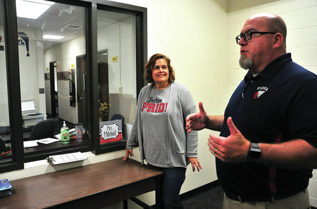 Michelle Mitchell listens to a security orientation by Tony Lyons at Piqua High School on Friday. Mitchell will be greeting visitors to Piqua High School and assisting them in gaining entry under the school's new security guidelines.