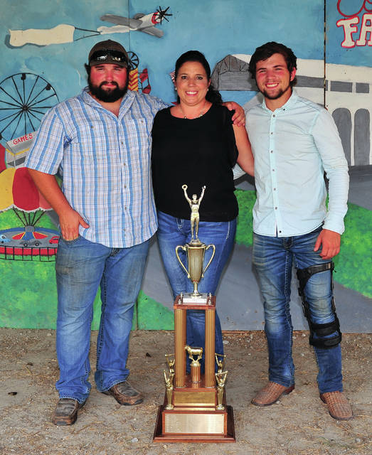 Mike Ullery | AIM Media Midwest A family of showmen, Kode, Julie, and Kamron Paulus pose with the traveling Sheep Showman of Showmen Trophy at the 2018 Miami County Fair. Kameron, who won the coveted title on Tuesday follows in the footsteps of his older brother Kodi, who won in 2011 and their mother, Julie, who was Showman of Showmen title in 1989. Their aunt Krista Stidham was also a Showman of Showmen winner.