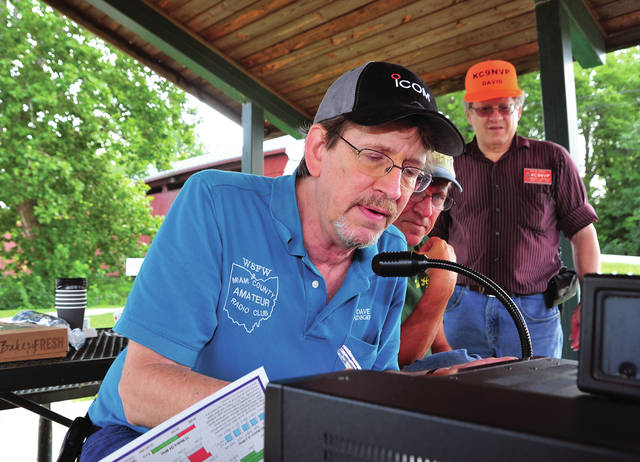 Mike Ullery | Daily Call Dave Ziegler of Piqua, KD8GEH; Kevin Ryan of Piqua, KE8CUU; and David Stein of Troy, KC9NVP, l-r, talk to other HAM Radio operators from the Eldean Covered Bridge on Saturday morning. HAM groups from several states set up operations at covered bridges in their area to talk, and more importantly, to test equipment. In the event of emergency, HAM radio is relied on by law enforcement, EMS, EMA, and FEMA to provide reliable communications when all other means are down. In their first hour of operation on Saturday, Miami County Amateur Radio Club members had made contact with more than a half-dozen operators in Ohio, Pennsylvania, and Kentucky.