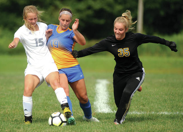 Lehman's Hope Anthony (19), and goalkeeper Hannah Giguere, (35) battle with Catholic Central's Caitlin Foley (5) for control of the ball against Catholic Central on Saturday at Lehman High School.