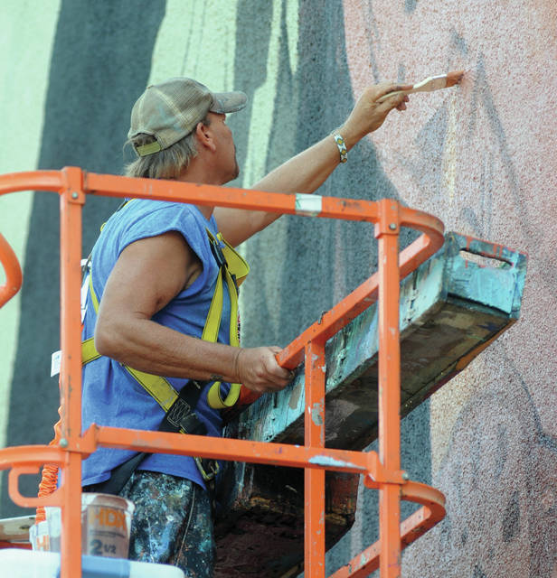 "Mike Ullery | Daily Call Artist Eric Henn works on the new downtown mural from atop a lift on Wednesday afternoon. The work is estimated to take another ""18-20 painting days"""