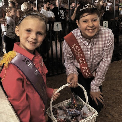 From left, Miami County Fair Princess Natalie Parke, 6, and Miami County Fair Pork Princess Abigail Maxson, 11, pass out candy and ribbons at the showmanship show Saturday morning.