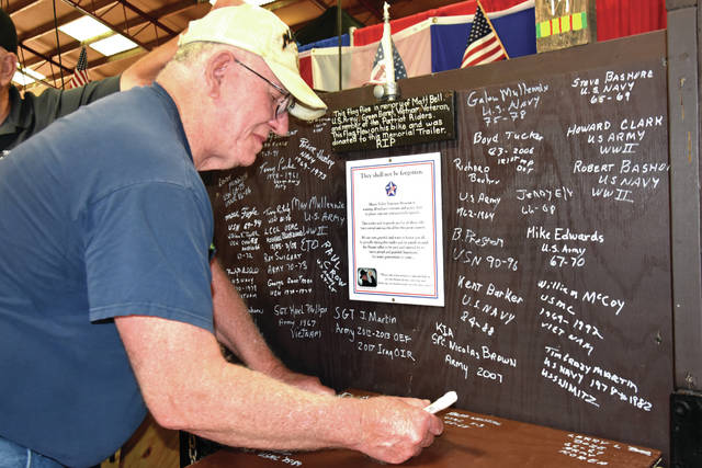 Cody Willoughby | AIM Media Midwest Ralph Westfall of Casstown, who served in the United States Marine Corps from 1966-68, signs one of the boards of the veterans memorial trailer on display at the Miami County Fair.