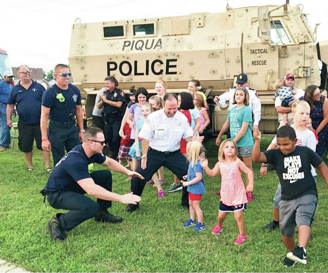 Mike Ullery | Daily Call Piqua firefighters and police officers dance with Indian Ridge residents at one of the National Night Out block parties held in neighborhoods throughout the city on Tuesday evening.