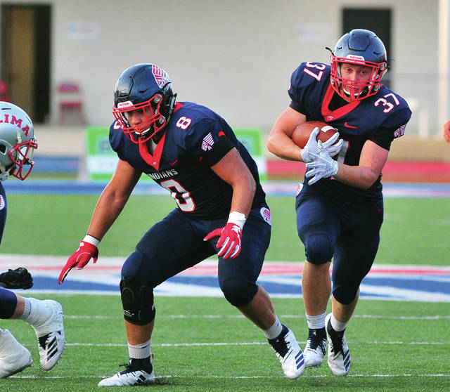 Mike Ullery/Call Photo Piqua running back Makeegen Kuhn follows the block of Jerell Lewis.