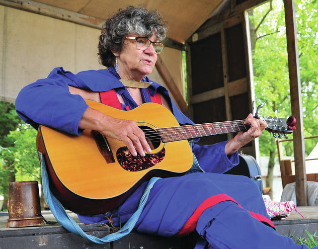 """Jane Cassidy, aka Buffalo Woman, who describes herself as a """"traveling nomad"""" plays a tune and sings in the mountain men encampment at Fort Rowdy on Saturday."""