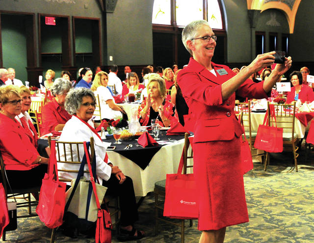 Mike Ullery | AIM Media Midwest Dr. Doreen Larson, president of Edison State Community College, opens Thursday's Go Red Goes North program at the Fort Piqua Plaza with a selfie of the crowd.