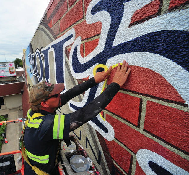 Mike Ullery | Daily Call Mural artist Eric Henn continues work on the downtown mural that will be over the Piqua Daily Call/Carried Away Salon/Quint's Signs building at the corner of East High and South Main streets. Henn expects the mural to be completed before the end of this month.