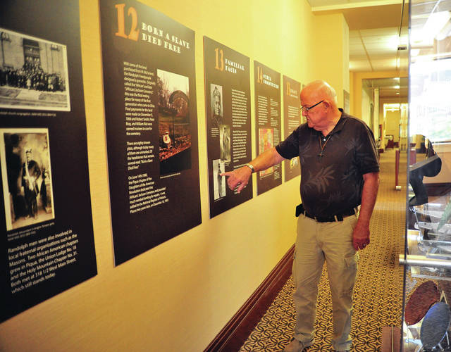 "Mike Ullery | Daily Call Gary Meek, historian at the Piqua Public Library, points out some of the history of the Randolph Freedpeople in a display at the library. The traveling exhibition, ""Freed Will: The Randolph Freedpeople from Slavery to Settlement,"" is on loan from the Ohio Historical Society and the Afro-American Museum & Cultural Center, and will be at the library through Nov. 1."