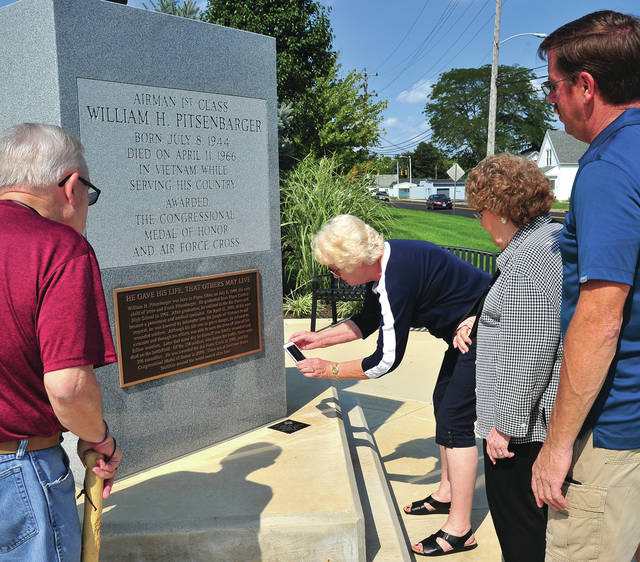 Mike Ullery | Daily Call Ruth Koon, center, uses her phone to scan the QR code recently installed at the base of the statue of Piqua Medal of Honor recipient William Pitsenbarger. The code will allow visitors to use their smart phones to hear details of Pitsenbarger's life and heroics. Watching Koon scan the QR code are fellow Friends of Piqua Parks board members Glenn Devers, Edna Stiefel, and Russ Fashner. The group hopes to generate interest in the QR technology to begin raising funds to install QR codes on other area points of interest.
