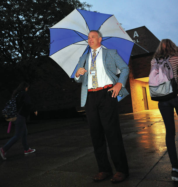 Mike Ullery | Daily Call Piqua High School principal Rob Messick, umbrella in hand, greets students as they arrive at school on Tuesday morning. Messick meets students every morning, rain or shine, offering a smile and good morning to all as they arrive.