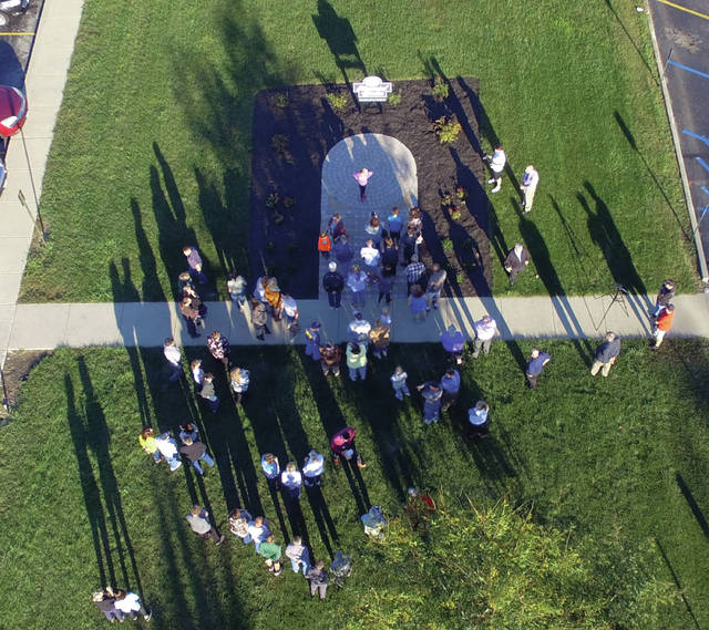 Piqua City Schools officials and family members gather at the dedication ceremony for the redesigned Memory Garden at Piqua High School on Wednesday. The garden honors and remembers Piqua High School students who died before they graduated.