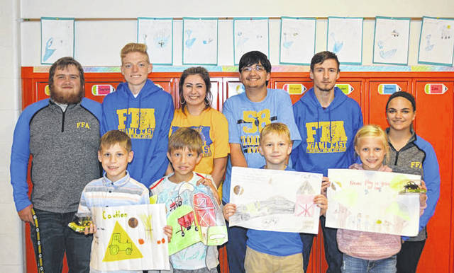 Provided photo Members of the Miami East-MVCTC FFA Safety Committee presented awards to Miami East Elementary second graders for their class winning farm safety posters. Members of the committee were, back row, left to right: Cody Niswonger, Lane Mergler, Brailyn Tarcea, Tyler Heckman, Daniel Baker, and Elizabeth Bair. Awards winners included, front, left to right, Beau Meyer, Cole Couser, Logan Howard, and Caitlin Howell.