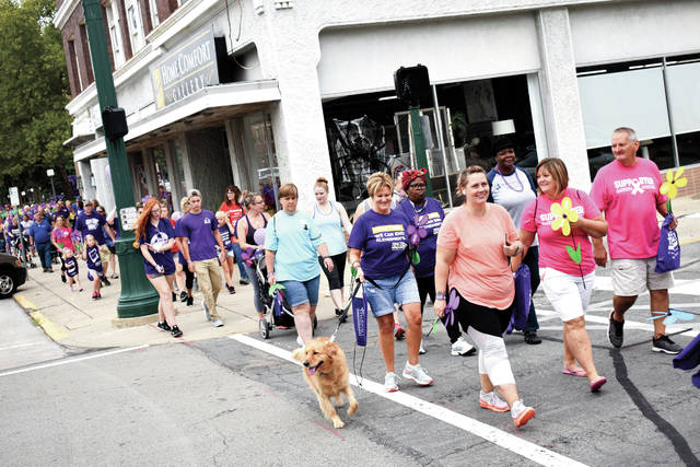 Cody Willoughby | AIM Media Hundreds of participants pace east on Main Street during the 15th annual Miami County Walk to End Alzheimer's on Saturday in downtown Troy.