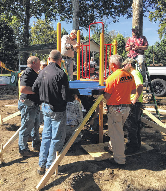 Sam Wildow | AIM Media Volunteers put together new playground equipment at the Covington Community Park over the weekend.