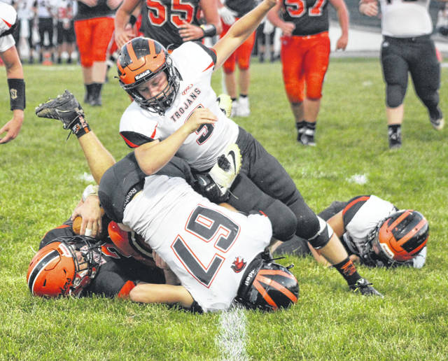 Arcanum's Dane Craport (67) wraps up Bradford runner Hunter Gheen early in the first half of Friday night's game at Bradford. The Trojans won the game 48-7.