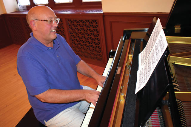 Cody Willoughby | AIM Media Director David Wion plays the piano in the third-floor ballroom at the Troy-Hayner Cultural Center. Wion accepted the position of director in early August.