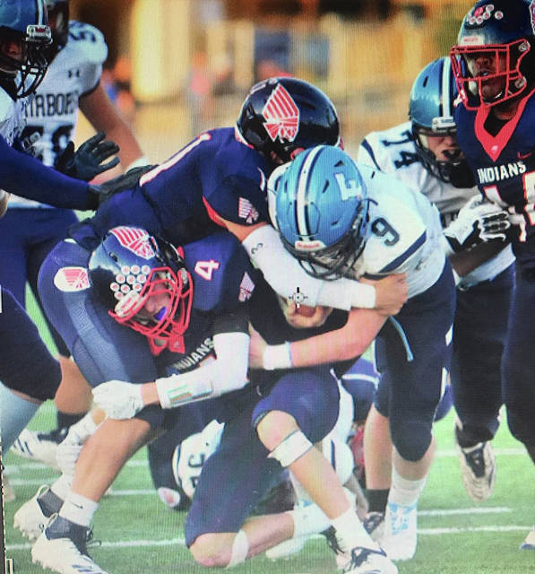 Mike Ullery/Call Photo Piqua's Mick Karn, Blane Ouhl (4) and Lance Reaves converge on Fairborn's Hunter Warner Friday night at Alexander Stadium/Purk Field.